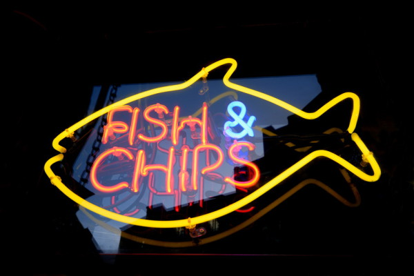 Striking yellow & orange neon sign for a fish and chips shop in Brighton